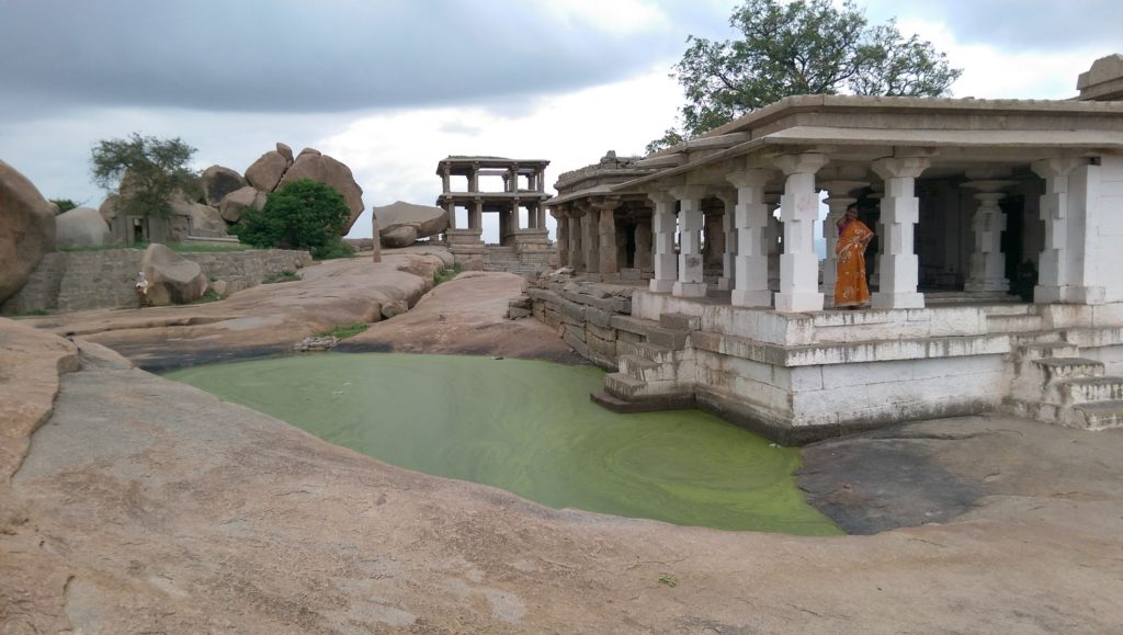 Hampi ruins, green water, woman